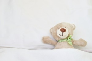 Cute bear lying on bed.