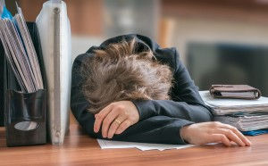 Tired and exhausted workaholic woman sleeping on desk in office.