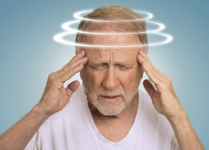 Headshot senior man with vertigo. Elderly male patient suffering from dizziness isolated on light blue background .