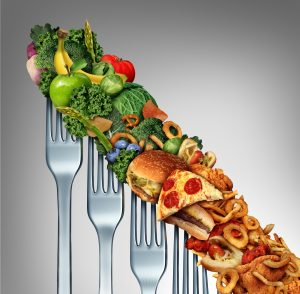 Diet relapse change as a healthy lifestyle slowly goes downward to greasy unhealthy fast food concept as a dieting quality decline symbol of returning to bad eating habits as a group of descending forks with meal items on them.