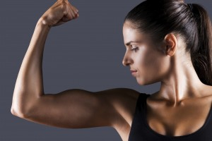 Perfect bicep. Beautiful young sporty woman examining her bicep while standing against grey background