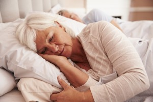 Senior Couple Lying Asleep In Bed Together