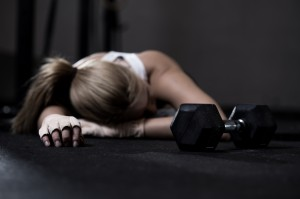 Young exhausted girl lying on a floor after training